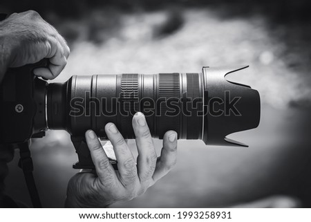 A person taking a photo, black and white photography.