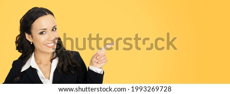 Happy smiling attractive woman in black confident suit, pointing showing advertising copy space area. Business concept. Orange yellow colour background. Brunette businesswoman. Wide banner image.  Royalty-Free Stock Photo #1993269728