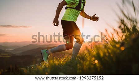 Cropped photo of Middle-aged mountain trail runner man dressed bright t-shirt with a backpack endurance running uphill by picturesque hills at sunset time. Sporty active people concept image.