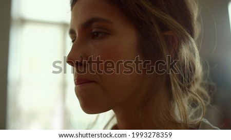 Thoughtful young woman painter biting lip in art studio on workshop. Inspired girl silhouette working on picture against window background. Talented female artist creating artwork indoors.