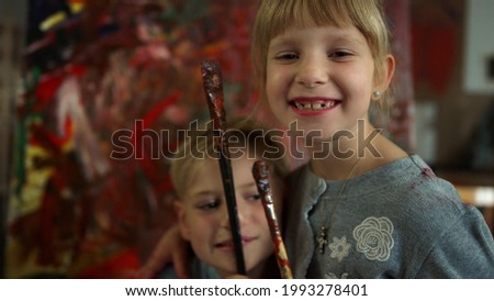 Joyful sister and brother posing on abstract picture background. Happy children looking to camera after workshop. Cheerful boy putting brush to nose in art studio.