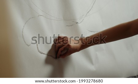Female artist hand drawing black line on white background. Unrecognizable girl making sketch for masterpiece in art studio. Unknown woman painter creating picture in workshop.