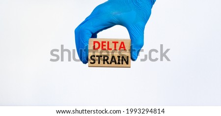 Covid-19 new delta strain symbol. Hand in blue glove holds wooden blocks words 'delta strain'. Beautiful white background. Copy space. Medical and COVID-19 new delta strain variant virus concept.