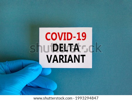 New covid-19 delta variant strain symbol. Doctor hand in blue glove with white card. Concept words 'covid-19 delta variant'. Medical and COVID-19 delta variant strain concept. Copy space.