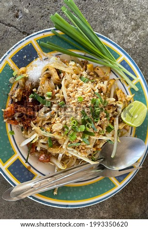 Picture of Pad Thai noodles, using cayenne pepper, sugar, and lime for seasoning.  with chives as a side dish  used for background