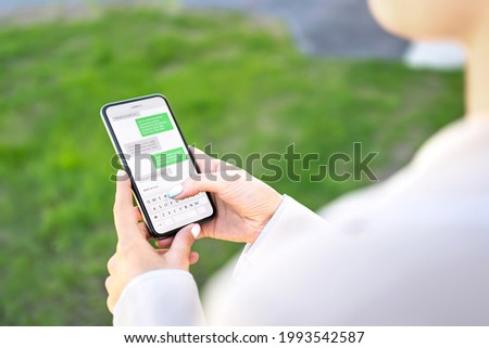 Woman texting with phone outdoors. Text message with smartphone. Digital sms and instant messaging chat. Person using cellphone in park outside in summer. Conversation with boyfriend or friend. Royalty-Free Stock Photo #1993542587
