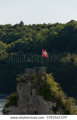 Swiss flag on a rock in the middle of the rhine falls near Schaffhausen in Switzerland 28.5.2021