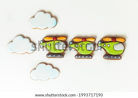 Gingerbread cookies in the shape of military helicopters flying in the clouds. Army or Men's day. Flat lay on white. Aviation day