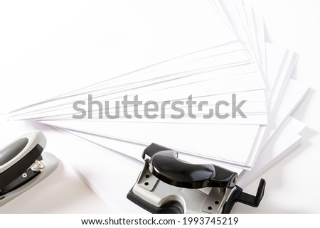 Photograph of some fan-shaped sheets of paper, a stapler and a hole punch for sheets of paper on a white background.The photo has free space to put text.The photo is taken in horizontal format.