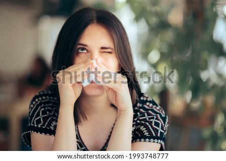 Allergic Woman Blowing her Nose with a Tissue Felling Sick. Person having a congested nasal obstruction symptom from allergy season  Royalty-Free Stock Photo #1993748777