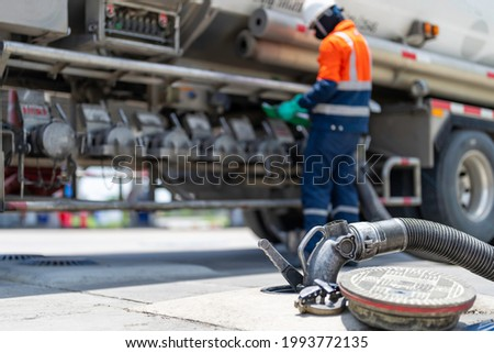 A tanker truck driver delivers gasoline to a gas station Royalty-Free Stock Photo #1993772135