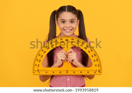 happy teen girl hold school math tool protractor ruler on yellow background, geometry