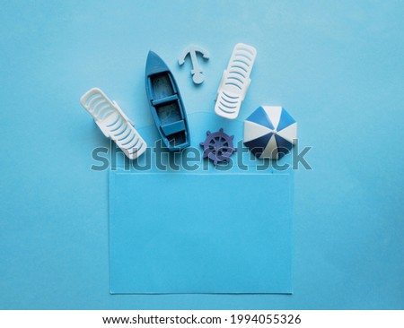 Blue envelope with sun lounger, beach umbrella, boat, anchor, steering wheel inside on a blue background.