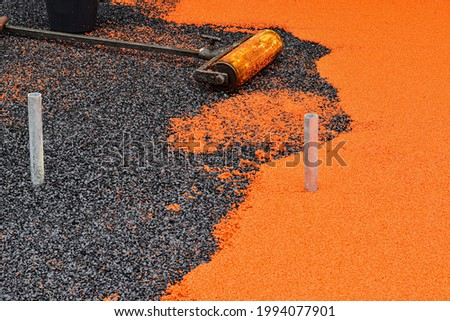 Side work. Construction side work. making a floor with the rubber beads on playground, New childrens playground under construction.  Flooring with the soft rubber bead. Royalty-Free Stock Photo #1994077901