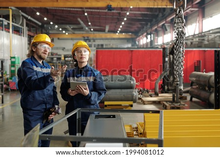 Bearded factory engineer in hardhat and safety goggles pointing at chains and explaining coworker how to use industrial crane Royalty-Free Stock Photo #1994081012