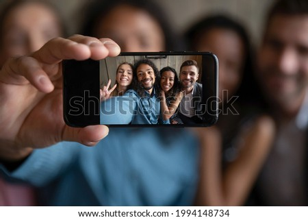Close up four diverse mixed race best friends posing for selfie, making photo on smartphone, having fun taking memory picture or recording funny video streaming in social network, friendship concept.
