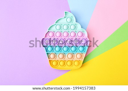 Trendy toy antistress, pop it on a rainbow background, fidget toy, top view Royalty-Free Stock Photo #1994157383