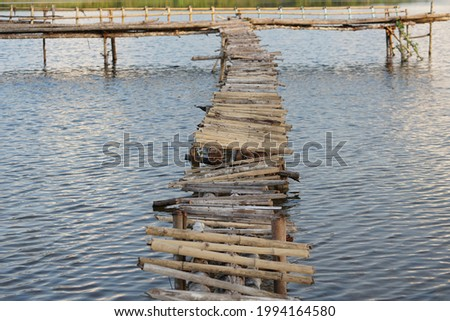 An old bamboo bridge jutting into the river For tourists taking pictures and enjoying the view