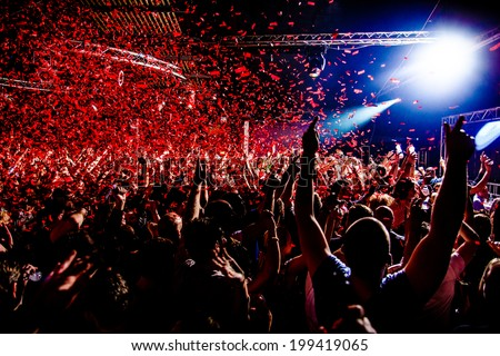 Nightclub party clubbers with hands in air and red confetti Royalty-Free Stock Photo #199419065