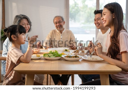 Big Asian happy family spend time having lunch on dinner table together. little kid daughter enjoy eating food with father, mother and grandparents. Multi-Generation relationship and activity in house Royalty-Free Stock Photo #1994199293