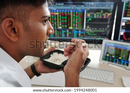 Serious trader eating lunch at office desk and looking at computer screen with stock market data