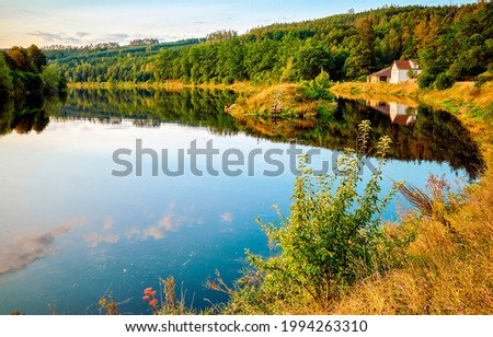Lake house on the shore of the autumn forest. Autumn lake in forest. Lake house in autumn scene Royalty-Free Stock Photo #1994263310