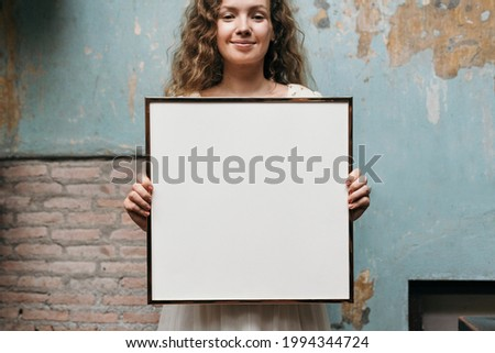 Cheerful woman holding a picture frame