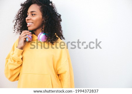 Beautiful black woman with afro curls hairstyle.Smiling model in yellow hoodie.Sexy carefree female enjoying listening music in wireless headphones.Posing on street background near wall