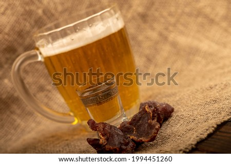 Pieces of dried caviar, a glass of vodka and a mug of beer on a table covered with a homespun cloth with a rough texture. Close-up, selective focus.