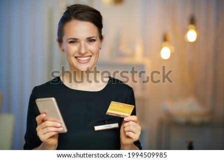 happy 40 years old woman worker with smartphone and credit card buying on internet in modern beauty studio.