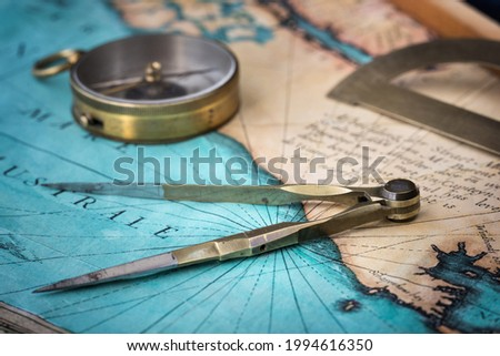 An old geographic map with navigational tools: compass, divider, protractor. View of the workplace of ship's captain. Travel, geography, navigation, tourism, history and exploration concept background Royalty-Free Stock Photo #1994616350