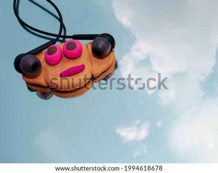 Head phone presented with clay made cartoon face on glass sky reflection surface