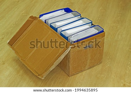 An open lidded cardboard box full of blue, thick office folders with documents and papers sits on the office floor. The archive is ready for relocation, transportation and storage
