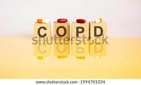 word COPD is made of wooden cubes on a yellow background with pills. medical concept of treatment, prevention and side effects. COPD - short for chronic obstructive pulmonary disease Royalty-Free Stock Photo #1994701034