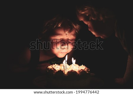 Dimly lit image of little boys blowing out candles on birthday cake in the dark with faces illuminated