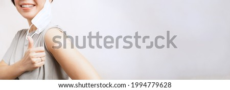 COVID-19 vaccination concept. Banner of a beautiful asian woman smiling and doing thumbs up after getting a Vaccine feeling okay and no side effect. Herd Immunity, Vaccinated, Hospital, Insurance Royalty-Free Stock Photo #1994779628