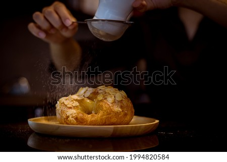 Cafe staff uses colander to sprinkle icing sugar croissants bake serving customers in the cafe.