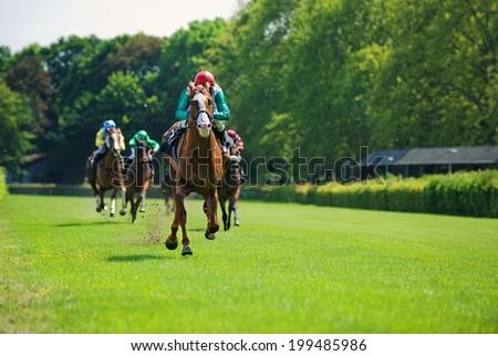 Race horses with jockeys on the home straight Royalty-Free Stock Photo #199485986