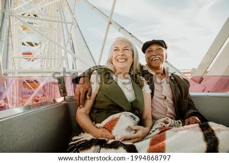Cheerful senior couple enjoying a Ferris wheel by the Santa Monica pier Royalty-Free Stock Photo #1994868797