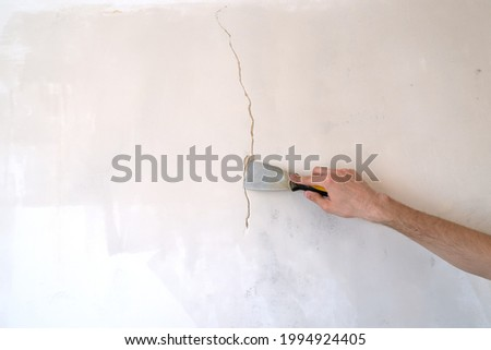 Construction man worker repairing a crack wall of a home, plastering cement on wall. Builder applying white cement to a crack in a wall with a putty knife. close up  Royalty-Free Stock Photo #1994924405