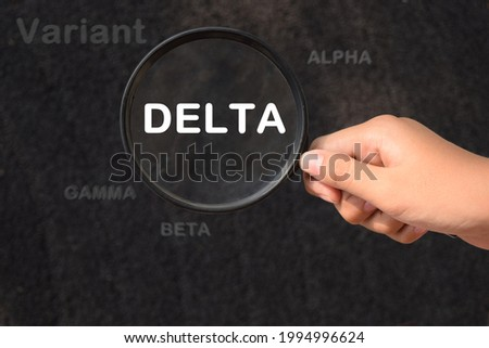New covid-19 delta variant strain symbol. Female holds a magnifying glass in his hand.