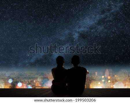 Silhouette of young Asian couple sit on wooden ground above the city under stars.