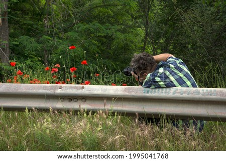 A Photographer Taking Picture of Poppies.