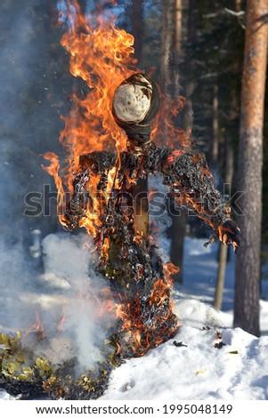 Burning scarecrow on festival maslenitsa. Slavic national spring pagan festival - Maslenitsa. Burning effigies straw on traditional holiday dedicated to spring - slavic celebration shrovetide