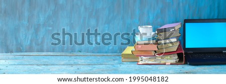 Stack of books, file folder and old laptop computer,home office, homeschooling,reading,education, business concept. Free copy space, panoramic