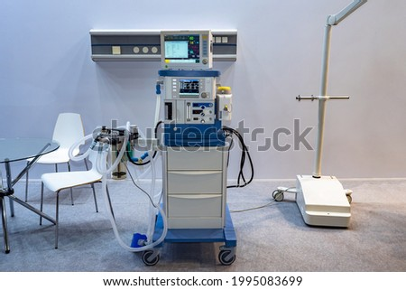 Anesthesia and respiratory apparatus in medical office. Anesthesia and respiratory apparatus showing with patient readings on monitor. Anesthesia and respiratory apparatus next to table. Royalty-Free Stock Photo #1995083699