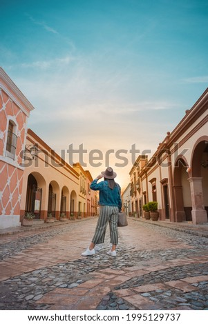 Tourist woman standing in the middle of the street of a magical town, town of La Peña del Bernal in Querétaro, Mexico, with sunset in front, summer day Royalty-Free Stock Photo #1995129737
