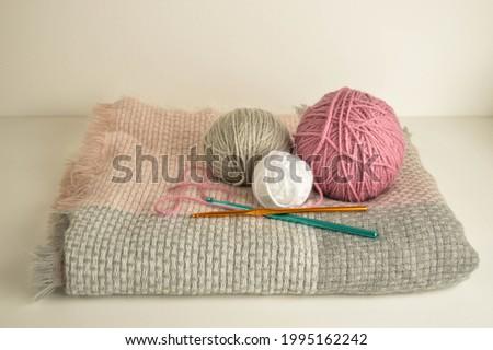 pastel woolen balls on winter scarf with crochet hooks