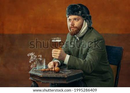 Drinking beer. Portrait of red headed and bearded man playing famous artist Van Gogh isolated on dark orange bacground. Concept of art, eras comparison, fashion. imitation, humor, ad. Bandaged ear. Royalty-Free Stock Photo #1995286409