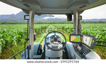 5G autonomous tractor working in corn field, Future technology with smart agriculture farming concept Royalty-Free Stock Photo #1995295766